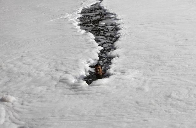 A man swims in the polluted waters of river Yamuna on a hot day in New Delhi May 29, 2013. REUTERS/Mansi Thapliyal/Files