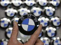 Сотрудник BMW держит в руках логотип компании на её заводе в Берлине 23 февраля 2015 года. Дивиденды, которые BMW планирует выплатить в этом году, оказались выше уровня 2013 года, когда компания заплатила 2,6 евро на одну обыкновенную акцию, но ниже прогнозов аналитиков, что вызвало снижение котировок акций на 1,97 процента до 117 евро по состоянию на 16.16 МСК. REUTERS/Fabrizio Bensch