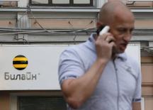 Мужчина говорит по телефону у офиса Билайна в Москве 28 мая 2012 года. Глава телекоммуникационной группы Вымпелком Джо Лундер уйдет в отставку 13 апреля, а новым главой назначен Жан-Ив Шарлье, сообщила компания в пятницу. REUTERS/Maxim Shemetov