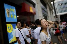 Customers stand outside of a McDonald's store in downtown Shanghai July 31, 2014. REUTERS/Carlos Barria