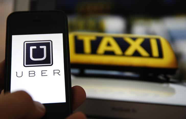 An illustration picture shows the logo of car-sharing service app Uber on a smartphone next to the picture of an official German taxi sign in Frankfurt, September 15, 2014. REUTERS/Kai Pfaffenbach