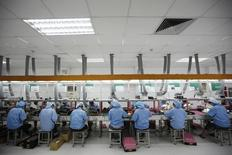 Employees work along a production line in Suzhou Etron Electronics Co. Ltd's factory in Suzhou, Jiangsu province in this June 8, 2010 file photo.   REUTERS/Aly Song/Files