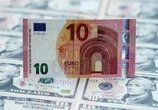 Банкноты евро и доллара США. Вена, 16 марта 2015 года. Евро во вторник растет к доллару второй день подряд, так как инвесторы ждут начала двухдневного заседания ФРС, которое покажет, стоит ли ждать повышения ключевой ставки в середине 2015 года. REUTERS/Heinz-Peter Bader