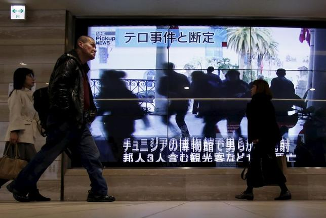 People walk past television screens displaying news coverage about Japanese tourists killed in an attack on the Tunisian national museum, on a street in Tokyo March 19, 2015. REUTERS/Yuya Shino