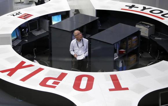 An employee of the Tokyo Stock Exchange (TSE) looks at a stock quotation board as he works at the bourse at TSE in Tokyo March 13, 2015. REUTERS/Yuya Shino