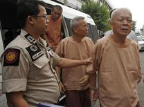 Opas Charnsuksai (R), 67, is escorted by prison officers as they arrive at the military court in Bangkok March 20, 2015. REUTERS/Chaiwat Subprasom