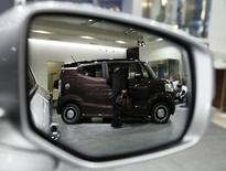 A man looking at the interior of Honda Motor Co's N-BOX SLASH vehicle is reflected in a side mirror of a car displayed at the company showroom in Tokyo January 30, 2015. REUTERS/Yuya Shino