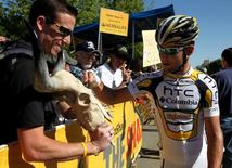 Mark Cavendish (R) of Britain autographs a cow skull for fan David Boyle of Lancaster, California at the starting line of the sixth stage of the Tour of California cycling race in Palmdale, California May 21, 2010. REUTERS/Anthony Bolante