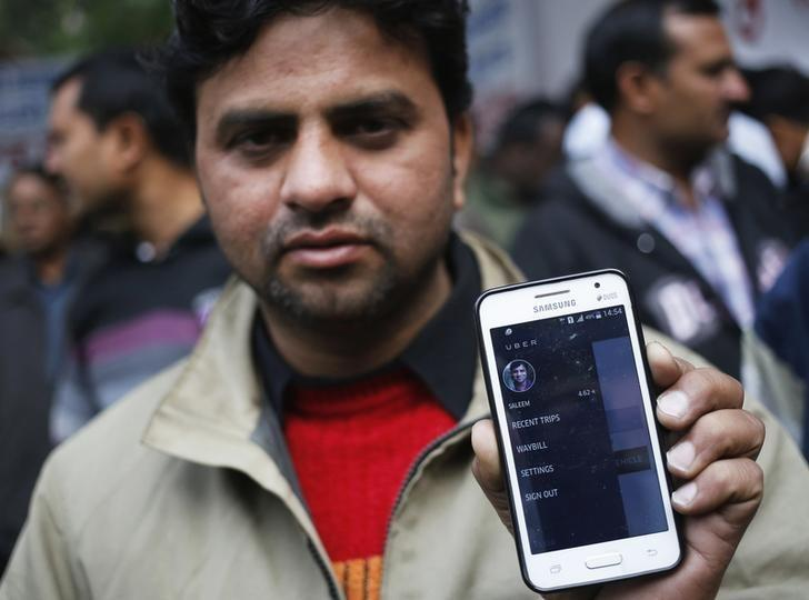 An Uber taxi driver shows an application software in his mobile phone used to track the taxi's location, during a protest against the ban on online taxi services, in New Delhi December 12, 2014. REUTERS/Anindito Mukherjee/Files