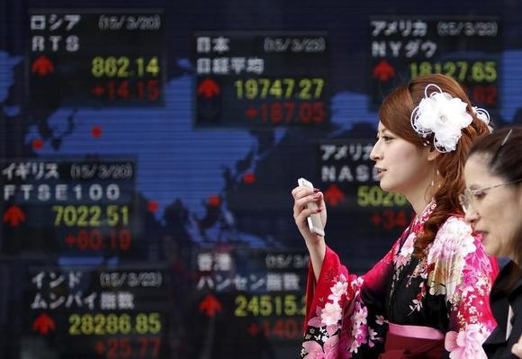 A woman wearing a Hakama, or Japanese traditional Kimono, holds her mobile phone as she walks past an electronic board, showing the stock market indices of various countries, outside a brokerage in Tokyo, March 23, 2015. REUTERS/Yuya Shino