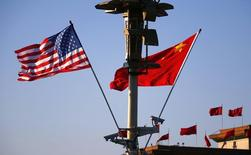 U.S. (L) and Chinese national flags flutter on a light post at the Tiananmen Square ahead of a welcoming ceremony for U.S. President Barack Obama, in Beijing, November 12, 2014. REUTERS/Petar Kujundzic