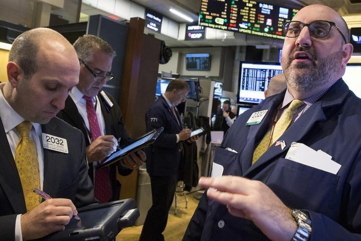 Specialist trader Peter Giacchi (R) gives a price just before the opening bell on the floor of the New York Stock Exchange March 26, 2015. REUTERS/Brendan McDermid