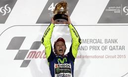 Yamaha MotoGP rider Valentino Rossi of Italy celebrates on the podium after winning the Qatar MotoGP Grand Prix at the Losail International circuit in Doha March 29, 2015.  REUTERS/Fadi Al-Assaad