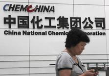 A woman checks her phone at the headquarters of China National Chemical Corporation in Beijing, July 20, 2009.  REUTERS/Stringer