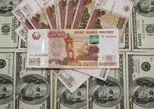 Банкноты российского рубля и доллара США. Сараево, 9 марта 2015 года. Рубль дешевеет к доллару на фоне отрицательной динамики нефти и укрепления валюты США на мировых рынках, а также после завершения накануне мартовского налогового периода, из-за чего предложение экспортной выручки в ближайшее время может сократиться, но одновременно торгуется в плюсе против евро, реагируя на текущее снижение единой валюты на форексе. REUTERS/Dado Ruvic