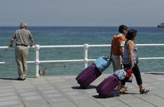 Paseo del Muro en la playa de San Lorenzo, Gijón, España, 6 ago, 2014. Los precios al consumidor en la zona euro cedieron en marzo en una tasa interanual como era previsto, según datos difundidos el martes, pero el declive fue pequeño, lo que sugiere que habrían tocado piso en enero y podrían comenzar a subir de nuevo pronto. REUTERS/Eloy Alonso