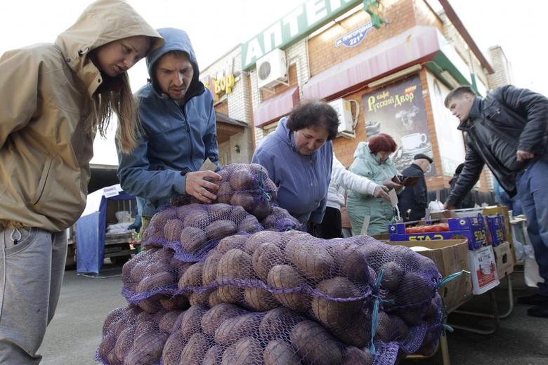 A vendor (R) sells vegetables at a food market, which operates once a week on Saturday, in the Russian southern city of Stavropol March 14, 2015.  REUTERS/Eduard Korniyenko