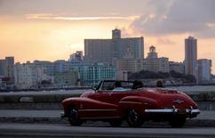 Tourists ride a convertible car on Havana's seafront boulevard El Malecon at sunset March 13, 2012.  REUTERS/Desmond Boylan