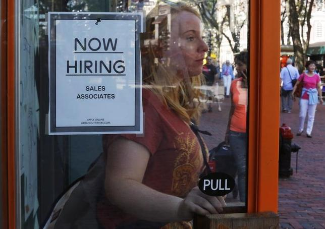 A woman walks past a ''Now Hiring'' sign as she leaves the Urban Outfitters store at Quincy Market in Boston, Massachusetts September 5, 2014.  REUTERS/Brian Snyder