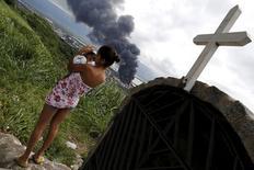 Una mujer sostiene un bebé mientras mira el incendio de tanques de almacenamiento de combustibles en el puerto de Santos. 3 de abril de 2015. Un incendio en una instalación de almacenamiento de combustible cerca de Santos, el mayor puerto de Brasil, entró en su cuarto día el domingo, mientras 110 bomberos trabajaban para impedir que las llamas se siguieran propagando, dijo el departamento de bomberos local. REUTERS/Nacho Doce     - RTR4W144
