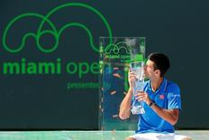 Apr 5, 2015; Key Biscayne, FL, USA; Novak Djokovic celebrates with the Butch Buchholz Champioship Trophy after his match against Andy Murray (not pictured) in the men's singles final on day fourteen of the Miami Open at Crandon Park Tennis Center. Geoff Burke-USA TODAY Sports