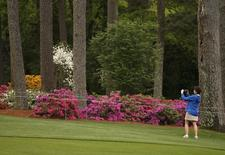 A golf patron takes pictures of the azaleas along the tenth fairway during a players practice round ahead of the 2015 Masters at the Augusta National Golf Course in Augusta, Georgia April 6, 2015.  REUTERS/Phil Noble