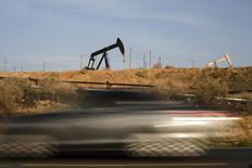 Машина проезжает мимо станка-качалки в Бейкерсфилде, США 18 января 2015 года. Цены на нефть снизились более чем на 1 процент в связи с резким повышением запасов нефти в США и рекордной добычей в Саудовской Аравии. REUTERS/Lucy Nicholson