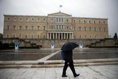 A man holding an umbrella walks in front of the parliament building during heavy rainfall in Athens March 13, 2015. REUTERS/Alkis Konstantinidis
