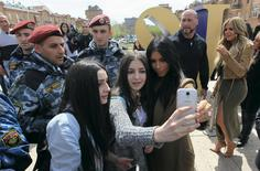 Kim Kardashian poses for a picture with local residents, with her sister Khloe standing nearby, while sightseeing in central Yerevan, April 9, 2015.  REUTERS/Vahram Baghdasaryan/PHOTOLURE