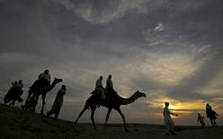 Tourists ride camels as they are silhouetted against the setting sun over the Thar Desert at Sam village on the outskirts of Jaisalmer in the desert Indian state of Rajasthan in this August 17, 2010 file photo. REUTERS/Krishnendu Halder