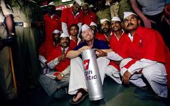 "Richard Branson, chairman of Virgin Atlantic, sits amid Mumbai's lunch couriers, known as ""dabbawalas,"" at a railway station in Mumbai, April 1, 2005. REUTERS/Arko Datta"