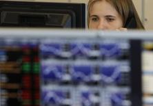 Трейдер в торговом зале инвестбанка Ренессанс Капитал в Москве 9 августа 2011 года. Российский фондовый рынок в пятницу следует заданной на этой неделе тенденции: валютный индикатор РТС покоряет новые вершины за счет укрепления рубля, а индекс ММВБ корректируется под давлением распродаж акций экспортеров. REUTERS/Denis Sinyakov