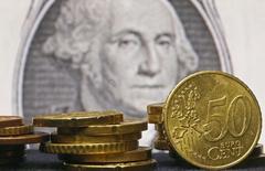 Monedas de euro fotografiadas frente a un billete de dólar en Zenica. Imagen de archivo, 13 marzo, 2015.  El euro cayó por quinta sesión consecutiva frente al dólar el viernes, tocando un mínimo de tres semanas y media, debido a que las menores tasas de interés europeas llevaron a los inversores al yen y a la moneda estadounidense. REUTERS/Dado Ruvic