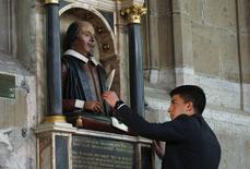 Christian Van Nieuwerburgh places a symbolic quill in the hand of a statue of William Shakespeare, marking the 450th anniversary of his birth inside Holy Trinity Church in Stratford-upon-Avon, in this file photo taken April 26, 2014.   REUTERS/Suzanne Plunkett/Files