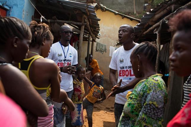 Social mobilizers speak with residents, including children during the three-day stay-at-home curfew in a slum in Freetown, Sierre Leone, in this UNICEF handout photo taken March 27, 2015. REUTERS/Bindra/UNICEF/Handout via Reuters