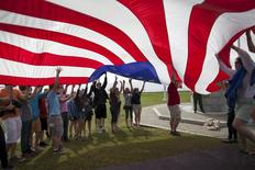 Students from Covenant Classical School of Concord, North Carolina, help raise a replica of a Civil War era American flag during the re-enactment of a flag-raising ceremony at Fort Sumter National Monument in Charleston, South Carolina April 14, 2015. REUTERS/Randall Hill