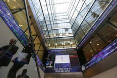 People pass electronic information boards at the London Stock Exchange in the City of London October 11, 2013. REUTERS/Stefan Wermuth