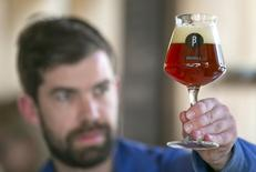 Sebastien Morvan, one of the founders of microbrewery Brussels Beer Project, inspects a glass of Babylone beer at Barbeton bar in central Brussels, April 14, 2015. REUTERS/Yves Herman