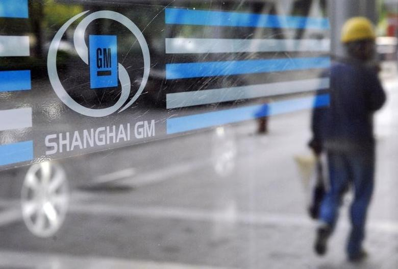 A labourer is reflected in the glass of a Shanghai General Motors exhibition hall in Shanghai in this file photo taken on May 28, 2009. REUTERS/Stringer