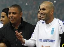 "United Nations Development Programme (UNDP) Goodwill ambassador Zinedine Zidane of France (R) gestures next to Brazilian Ronaldo before the eighth ""Match Against Poverty"" soccer match in Piraeus, near Athens in this file photo taken on December 14, 2010. REUTERS/Yiorgos Karahalis"