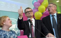 """Глава партии """"Финляндский центр"""" Юха Сипиля (в центре) вместе с однопартийцами в предвыборном штабе партии в Хельсинки. 19 апреля 2015 года. Бизнесмен-миллионер, разрекламированный как технократ, способный вывести Финляндию их экономического спада, выиграл в воскресенье парламентские выборы, но ему, вероятно, потребуется коалиционная поддержка партии евроскептиков, занявших второе место. REUTERS/Markku Ulander/Lehtikuva"""