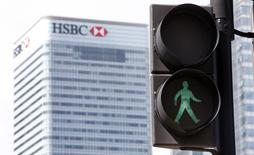 The HSBC building is seen in the background as the green man flashes at a pedestrian crossing in East London April 17, 2015.   REUTERS/Cathal McNaughton