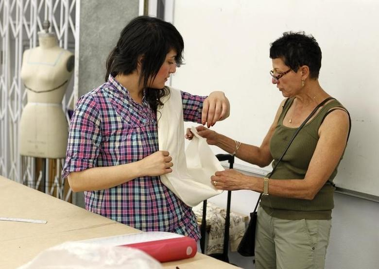 A Student Works With Her Instructor R In The Fashion Design Program At