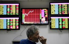 An investor looks back in front of computer screens showing stock information at a brokerage house in Wuhan, Hubei province April 20, 2015. REUTERS/Stringer