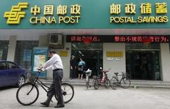 A man pushes his bicycle past a branch of China Post's Postal Savings Bank of China in Wuhan, Hubei province May 4, 2012. REUTERS/Stringer