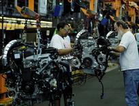 Unos trabajadores en la planta de ensamblaje de vehículos de Ford en Louisville, EEUU, jun 13 2012. El crecimiento económico de Estados Unidos se apresta a repuntar durante el segundo trimestre, aunque la fortaleza del dólar podría quitarle impulso y sumar argumentos para que la Reserva Federal empiece a elevar su tasa de interés clave más adelante este año, mostró un sondeo de Reuters.    REUTERS/John Sommers II