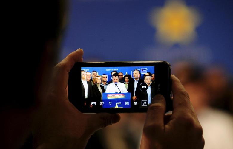 Opposition leader Zoran Zaev (C) is seen on a mobile phone screen during a news conference in Skopje April 14, 2015. REUTERS/Ognen Teofilovski