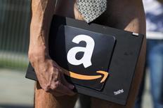 Мужчина держит ноутбук с логотипом онлайн-ритейлера Amazon на акции протеста в Берлине 5 сентября 2013 года. Выручка Amazon.com Inc в первом квартале выросла сильнее ожиданий благодаря подъему продаж в Северной Америке и растущему бизнесу облачных сервисов, что подняло акции компании примерно на 7 процентов. REUTERS/Thomas Peter