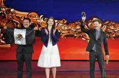 Diretor mexicano Bernardo Arellano levantando prêmio ao lado de membros do elenco, em Pequim.   24/04/2015     REUTERS/Stringer