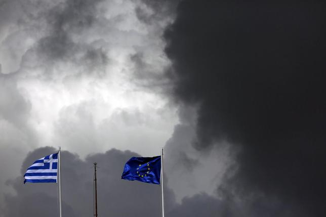 A European Union flag (R) and a Greek national flag flutter atop a building in central Athens March 28, 2015. REUTERS/Kostas Tsironis